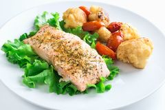 Salmon with vegetables on white plate Stock Photos