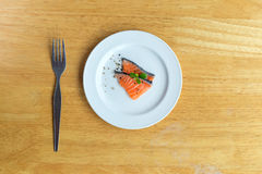 Salmon in white dish and fork on table. Salmon in white dish and fork on wooden Royalty Free Stock Photography
