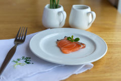 Salmon in white dish and fork on table. Salmon in white dish and fork on wooden Royalty Free Stock Images
