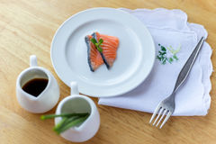 Salmon in white dish and fork. On wooden Royalty Free Stock Photo
