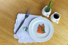 Salmon in white dish and fork on wooden. Salmon in white dish and fork Stock Images