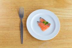 Salmon in white dish and fork on wooden. Salmon in white dish and fork Stock Image