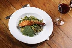 Salmon with wild garlic pasta. And redwine Stock Image