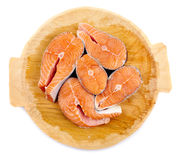 Salmon on wooden board. Salmon slices on a wooden board isolated on white background Royalty Free Stock Image
