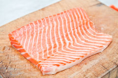 Salmon on wooden chopping board Stock Image