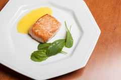 Salmon on a wooden table. Salmon grilled with arugula leafs and parsnip cream on a wooden table Royalty Free Stock Photo