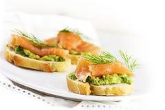 Salmone affumicato e crema o guacamole dell'avocado sulle fette delle baguette Immagini Stock Libere da Diritti