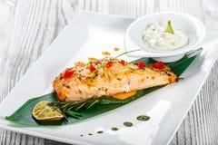 Salmone al forno con la salsa, i rosmarini ed il limone di formaggio su fondo di legno Piatto di pesci caldo immagini stock