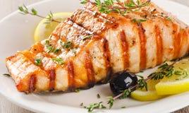 Salmone arrostito con il limone, le olive e le erbe fresche immagini stock libere da diritti