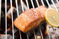 Salmone arrostito con il limone sul fiammeggiare fotografia stock