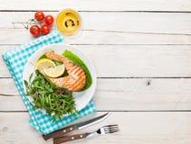 Salmone arrostito e vino bianco sulla tavola di legno fotografie stock libere da diritti