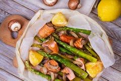Salmone, asparago, funghi e limone in pergamena Vista da sopra, colpo superiore dello studio Fotografia Stock