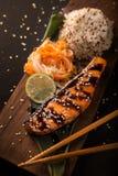 Salmone di Teriyaki con riso su un vassoio di legno top Fotografia Stock