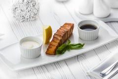 Salmone fritto del pesce con il limone e una salsa di soia immagini stock libere da diritti