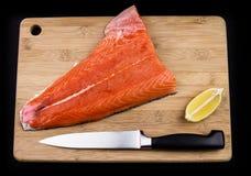 Salmone su un tagliere, su un coltello e su un limone Fotografia Stock Libera da Diritti
