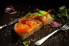 Salmones adobados con las semillas de la albahaca y de sésamo en la rebanada de pan Fotografía de archivo
