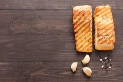 Salmones asados a la parrilla con el ajo, pimienta, sal en fondo de madera Fotografía de archivo libre de regalías