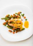 Salmones cocidos con las habas verdes, las zanahorias, los guisantes verdes, el tomillo y la salsa anaranjada en una placa blanca Fotos de archivo