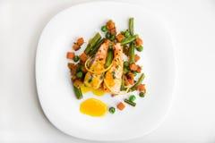 Salmones cocidos con las habas verdes, las zanahorias, los guisantes verdes, el tomillo y la salsa anaranjada en una placa blanca Foto de archivo libre de regalías