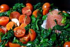 Salmones con espinaca y tomates Foto de archivo libre de regalías