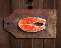 Salmones crudos en tabla de cortar de madera Imagen de archivo libre de regalías