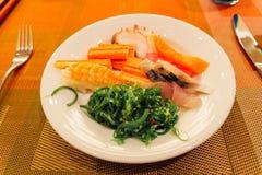 Salmones de la cena de Japanesse de los mariscos, atún, palillo del cangrejo, sushi, alga marina en una placa en el hotel Imagen de archivo libre de regalías