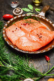 Salmones en cacerola frita con los ingredientes en la tabla de cocina rústica Fotografía de archivo