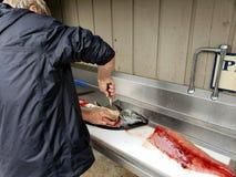 Salmones que cortan del hombre Imagen de archivo