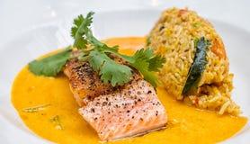 Salmones y arroz con una salsa amarilla Foto de archivo