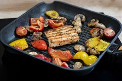 Salmones y verduras deliciosos en la parrilla Primer en el asado a la parilla de las pimientas de color salmón, rojas y amarillas fotos de archivo
