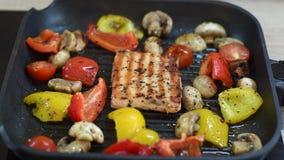 Salmones y verduras deliciosos en la parrilla Primer en el asado a la parilla de las pimientas de color salmón, rojas y amarillas almacen de video