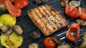 Salmones y verduras deliciosos en la parrilla Primer en el asado a la parilla de las pimientas de color salmón, rojas y amarillas metrajes