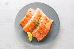Salmoni Limone crudo del peper dell'erba delle bistecche di color salmone sul BAC bianco del calcestruzzo fotografie stock libere da diritti