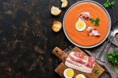 传统西班牙安达卢西亚的蕃茄奶油汤- salmorejo 素食蕃茄汤 从上面,平的位置的看法 库存图片