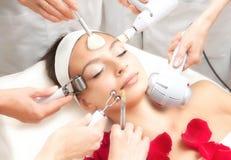 Salón del balneario: Mujer hermosa joven que tiene diverso tratamiento facial Imagenes de archivo
