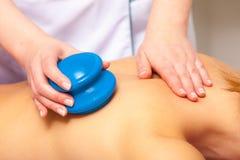 Salón del balneario. Mujer que se relaja teniendo masaje del ahuecar-vidrio. Bodycare. Imagen de archivo libre de regalías
