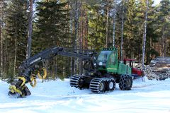 Wheeled Harvester by Forest Logging Site. SALO, FINLAND - MARCH 3, 2013: Wheeled harvester and skidder by logging site in Salo, Finland on March 3, 2013. The EU Royalty Free Stock Photography