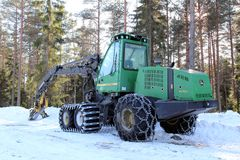 Wheeled Harvester by Forest Logging Site. SALO, FINLAND - MARCH 3, 2013: Wheeled harvester and skidder by logging site in Salo, Finland on March 3, 2013. The EU Royalty Free Stock Images