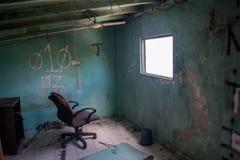 Salon avec la chaise devant la fenêtre dans la maison brûlée abandonnée ruinée Image libre de droits