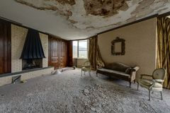 Salon avec la cheminée, le divan et les chaises - station de vacances abandonnée de Nevele - montagnes de Catskill, New York Photos stock