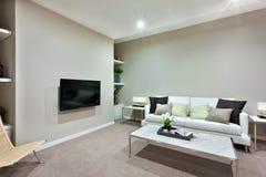 Salon avec une table blanche et des sofas avec des oreillers d'une maison luxueuse image libre de droits
