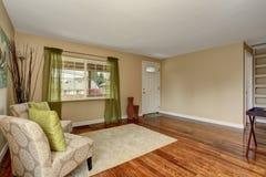 Salon beige confortable avec le plancher en bois dur brillant et le rideau vert Photographie stock libre de droits