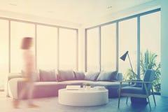 Salon blanc avec un sofa bleu, coin, fille Images libres de droits