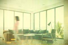 Salon blanc avec un sofa gris, fille latérale Photographie stock