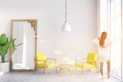 Salon blanc de fauteuils jaunes, miroir, femme Images stock