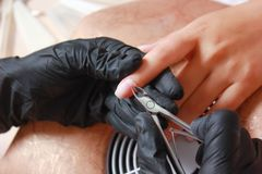 Salon de clou Plan rapproché de main femelle avec les ongles naturels sains obtenant la procédure de soin d'ongle Élimination de  Images libres de droits