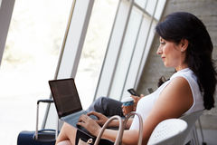 Salon de départ d'aéroport d'Using Laptop In de femme d'affaires Photographie stock