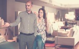 Salon de visite de couples de famille des meubles à la recherche du nouveau divan image stock
