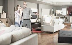 Salon de visite de couples de famille des meubles à la recherche du nouveau divan photos stock