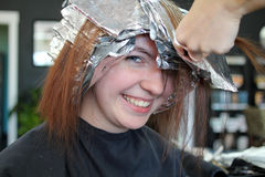 Salon Highlights. Happy teen girl getting full foil highlights at salon Royalty Free Stock Images